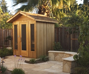 """""""Our outdoor Sauna [....] includes an unassembled cedar shingle roof package. You supply the waterproof pad and we provide the insulated modular room. Outdoor Saunas may be assembled on a concrete pad or on a deck. If installing on a deck first put down a sheet of ¾"""" plywood covered by vinyl or use concrete board with tile. The roof package includes wood plates, prefab rafters, nailers, facing, metal flashing, cedar shingles, ridge cap, and nails. You put it together. It includes the same…"""