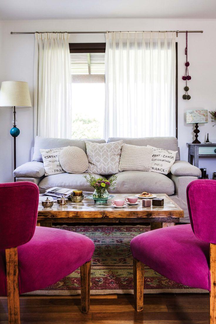 Living romántico en colores pasteles con acentos en fucsia y alfombra dada vuelta para suavizar los colores.