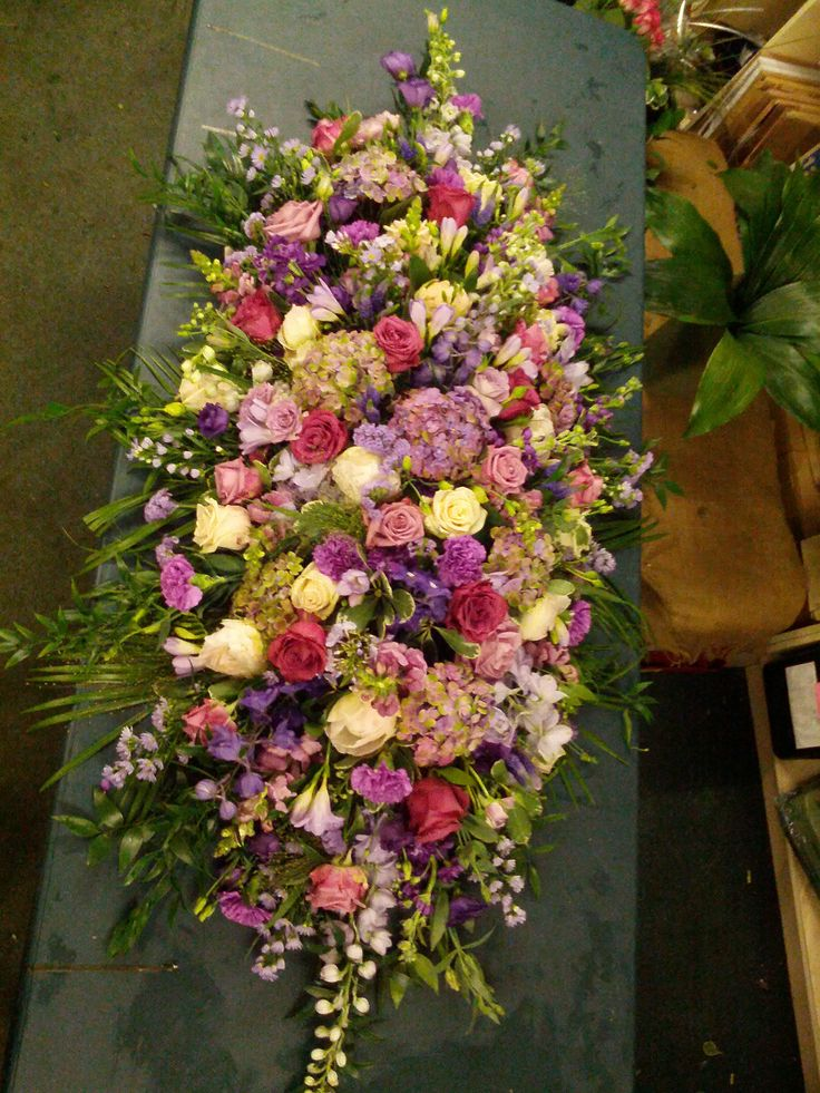 pink and lilac coffin spray with roses, hydrangeas,  delphiniums, freesia, carnations,