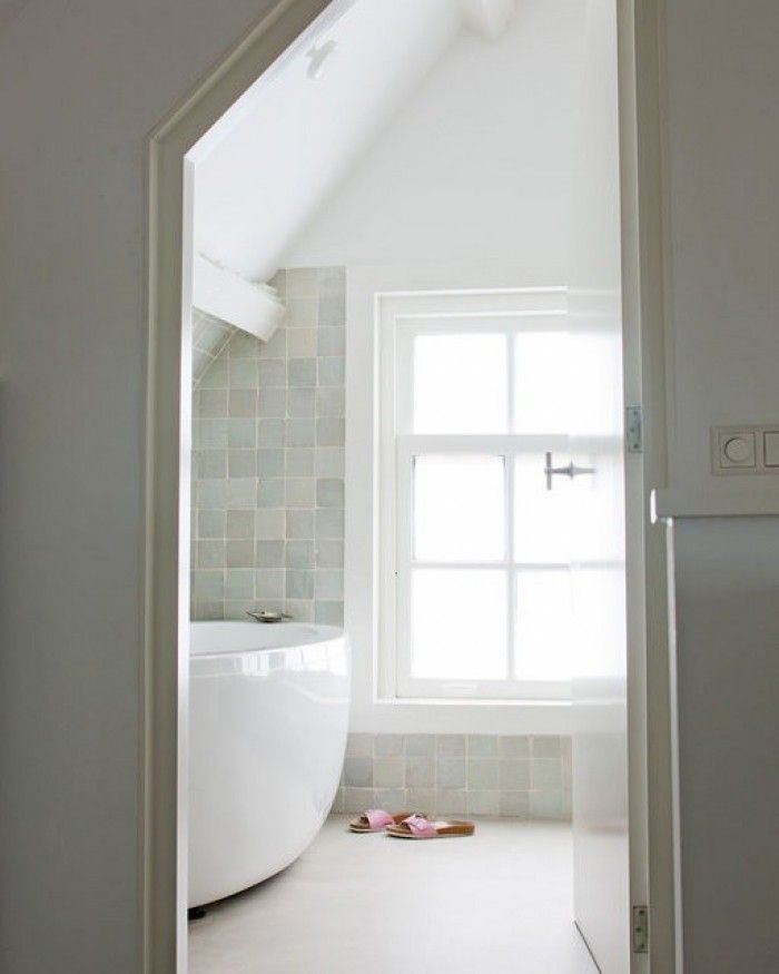 neutral naturals and a spray of white- love the sharply sloped ceilings and white washed beams. The floor disappears and the tub could easily be a boat... Where are the white, gauzy drapes?