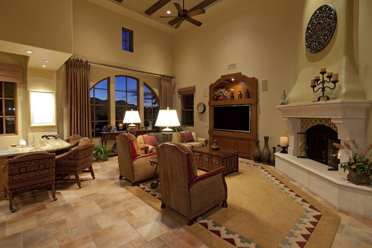 Large living room space features bar area in one corner, fireplace in opposite, with stone flooring, patterned aztec style rug, and exposed beams on two story height ceiling.