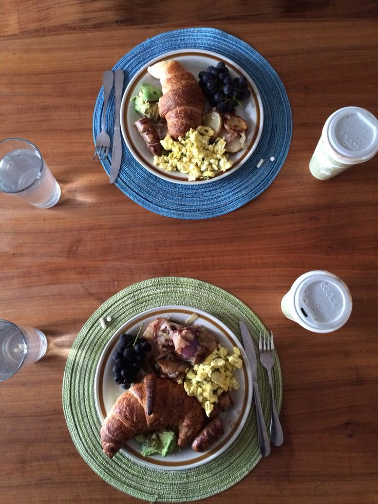 A perfect breakfast. Sausage, avocado, eggs, potatoes, grapes, croissant, green teas.