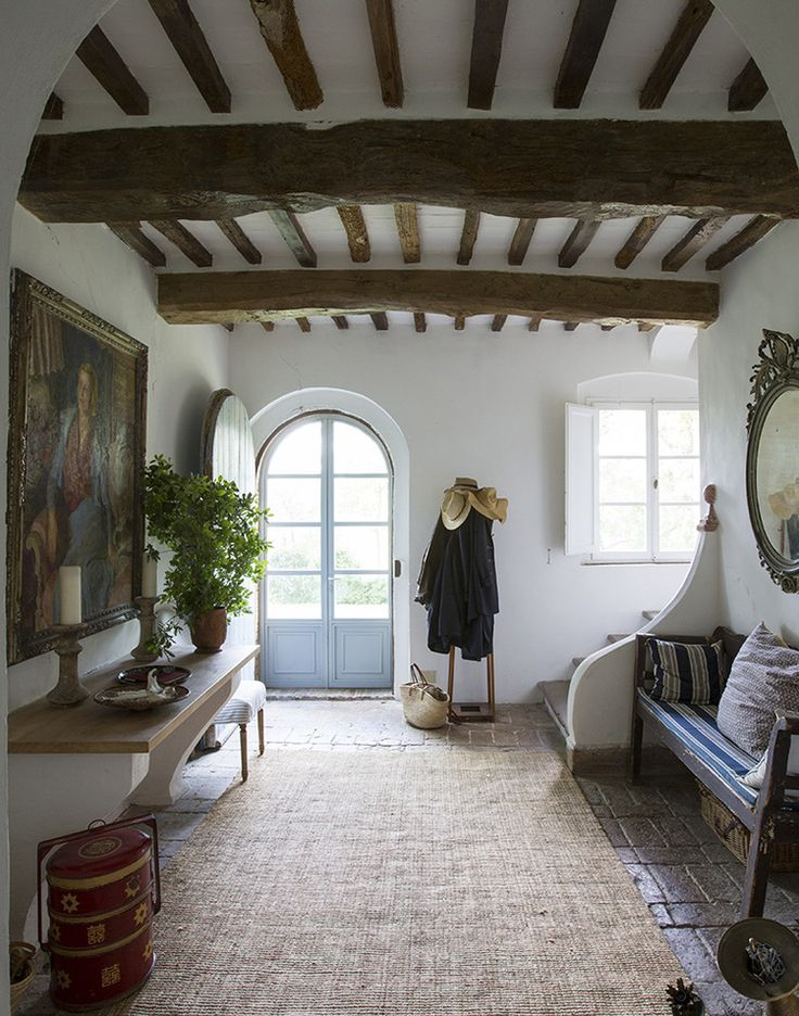 European farmhouse entry foyer with arched front door, rustic decor, and beamed ceiling. #europeanfarmhouse #entry #archeddoor #interiordesign #rusticdecor #farmhousestyle