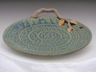 """This Platterwas wheel-thrown using an high-fired stoneware. It is finished with our signatureteal ash glaze. The handle is clay """"vine""""-looking, with a leaf a"""