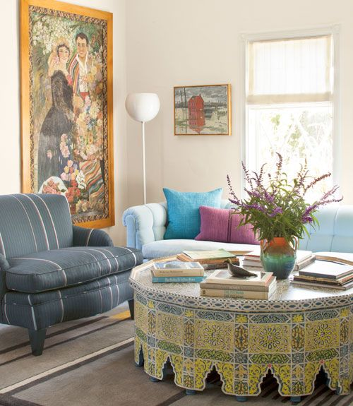 A painted-wood Moroccan table strikes an exotic note in the living room. Paul Smith suiting wool covers the low-slung 1940s chair; baby-blue velvet updates the 1960s Dunbar sofa. Emerson scored the flamboyant oil portrait at an estate sale.   - CountryLiving.com