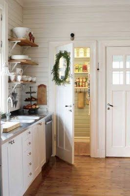 White kitchen, natural wood open shelving, zinc countertops, wood floors.
