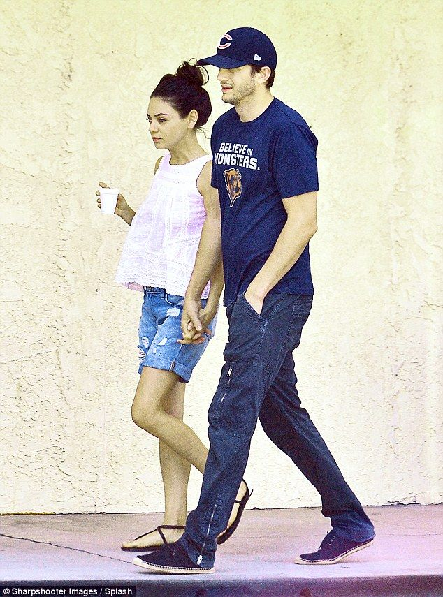 Taking it slow! Mila Kunis and her husband Ashton Kutcher held hands during a relaxed stroll through Studio City on Monday
