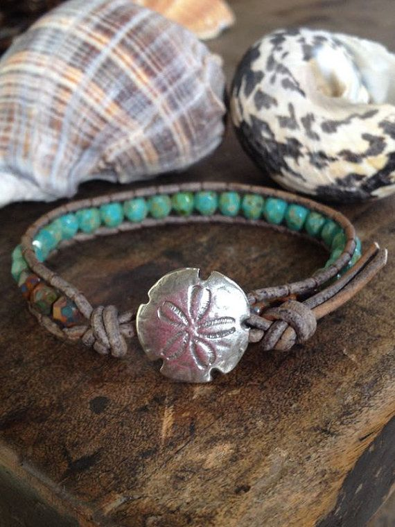 Gorgeous multi faceted turquoise and brown Picasso Czech beads are handwoven onto distressed leather cord featuring a beautiful sand dollar clasp.