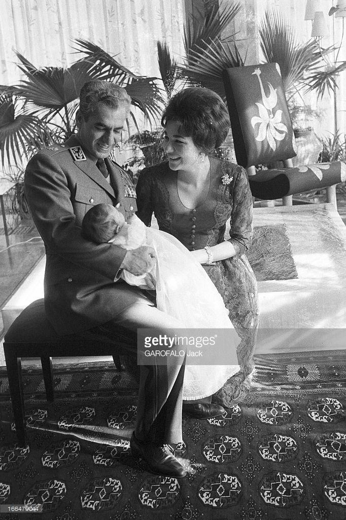 Rendezvous With The Shah Of Iran, Farah And Their Son Reza Cyrus Pahlavi. Téhéran- 7 Décembre 1960- La famille impériale: le Shah en uniforme militaire, assis, portant sur ses genoux son fils nouveau-né Reza Cyrus PAHLAVI vêtu d'une robe de voile blanc, son épouse Farah DIBA à ses côtés.