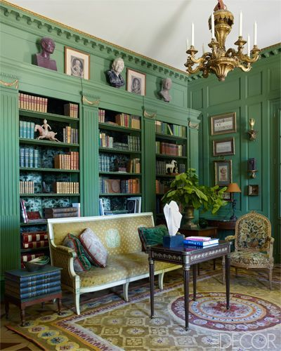 The library of a French château decorated by Michael Coorengel and Jean-Pierre Calvagrac features a Directoire sofa that retains its original velvet, a 19th-century table and chandelier, and an 18th-century armchair with its orginal needlepoint upholstery; the paneling is painted in Canopee by Zuber.