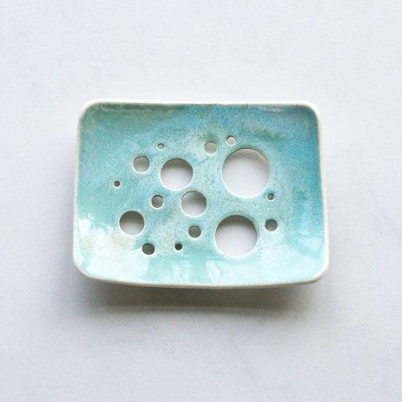 Porte-savon en porcelaine céramique fait à la main avec un aqua glacis et bulle de trous.  Courbe de forme pour tenir la plupart des savons. Turquoise / aqua vernis brillant. Trous pour drainer le savon. Pieds boule de porcelaine. Savon à vaisselle 80 x 104 mm env.  S'il vous plaît permettre pour avoir de légères différences dans la glaçure en raison de processus sont fait-main. Le vôtre sera tout aussi beau que ceux indiqués.  En tant que graphiste, je suis habitué à la conception de logos…