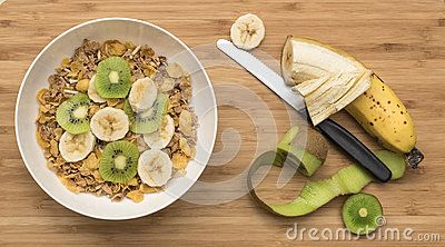 A white bowl of multi grain breakfast cereal on a cutting board with a knife. The cereal is topped with slices of  kiwi fruit and banana.