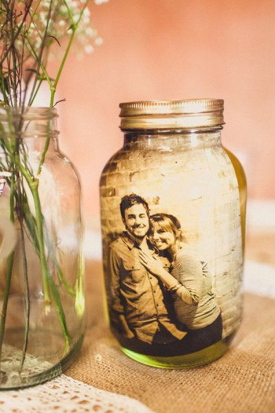 Laminate pictures and put in mason jars filled with water. Beautiful wedding idea!