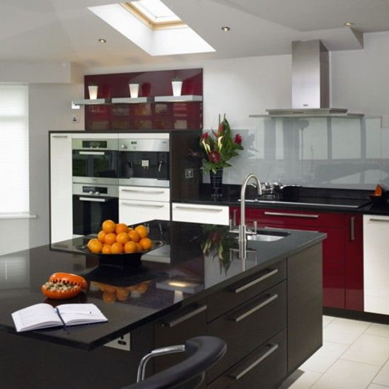 Mixing wine red and black with white, this kitchen has managed to achieve a modern look with out feeling too cool and stark- the red warms up the black and the white keeps the room feeling light and airy.