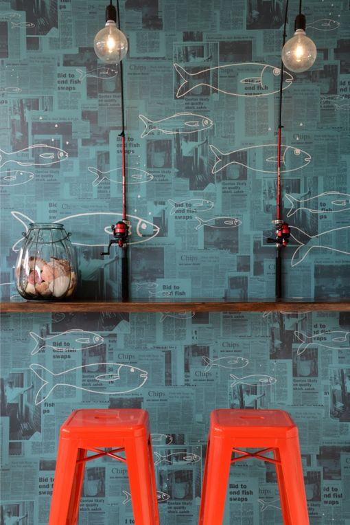 Lampes montées sur cannes à pêche, journaux tapissés au mur et lazurés en bleu, poissons dessinés au posca blanc, tabourets métalliques un peu fluo sur les bords : cocktail d'ambiance iodée…