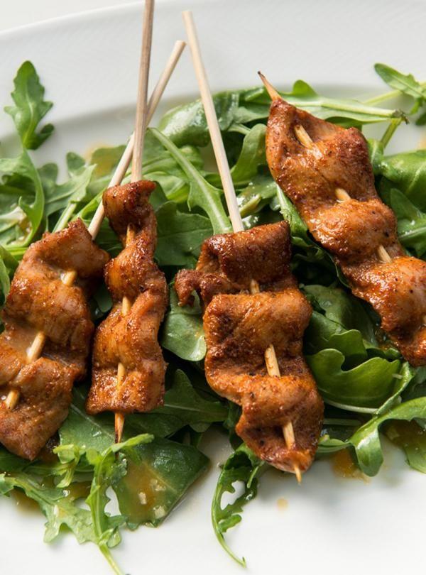 Recette de Ricardo de brochettes de porc aux épices sur salade de roquette