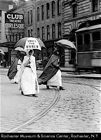 "group of marchers on Main Street West in August 1914 suffragist parade wearing yellow dominoes & carrying yellow parasols. 1st group in yellow & blue dominoes advertised speech & visit of Dr. Anna Howard Shaw. 2nd group carried placards with names of equal suffrage states & dates when they adopted votes for women. The Club Theatre with ""Burlesque"" sign occupies 75 Main Street West formerly occupied by the Shubert Theatre."