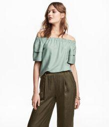 CONSCIOUS. En bluse i vevd kvalitet av Tencel® lyocellblanding. Blusen har elastikk øverst med bare skuldre og korte, doble ermer. Avrundet nederst.