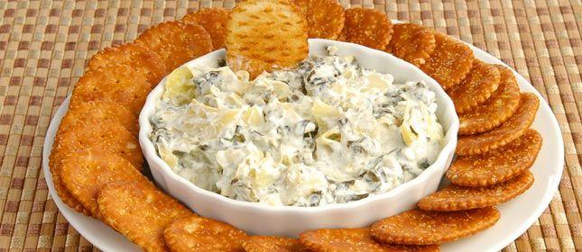 El dip de espinacas y alcachofas también lleva queso parmesano, Para 6-8 personas Ingredientes ¾ de taza de espinacas congeladas y troceadas 1 ¼ de taza de corazones de alcachofas congelados y picados finamente 140 gr de queso crema 1/4 taza de mayonesa ¼ de taza de queso parmesano rallado ¼ de cucharadita de ají molido ¼ de cucharadita de ajo en polvo 1 pizca de sal Galletas o nachos