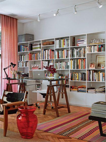 No escritório, integrado ao estar, o tampo de vidro se apoia em dois cavaletes de madeira (Velha Bahia). A estante (Ovo) é um móvel solto da parede e pode ser trocada de lugar. Banqueta vermelha da Kartell e poltrona Kilin, de Sergio Rodrigues