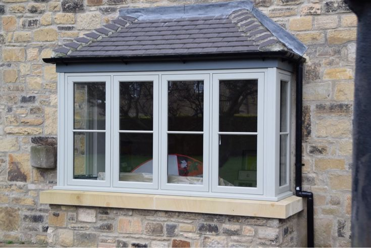 Flush-fitting casement bay windows factory-finished in grey.