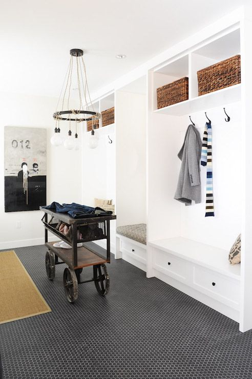 Vintage mudroom features a Schoolhouse Electric Tangled Chandelier hanging over a vintage cart doubling as shoe rack atop black penny floor accented with white grout.