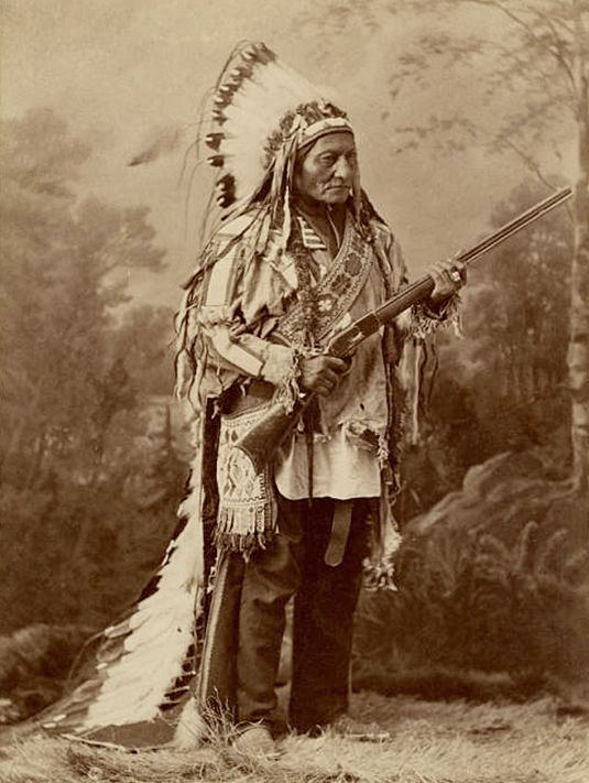 Sitting Bull wearing a war bonnet and holding a rifle as he stands in front of a painted backdrop. Handwritten captions.