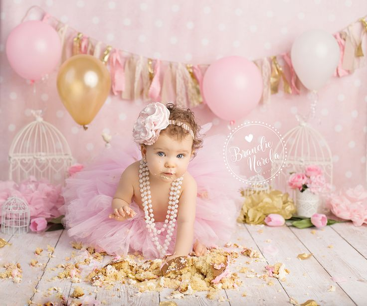 Baby smashing cake in pink tutu and a pearl necklace in themed baby cake smash photo by Brandie Narola Photography