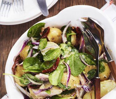Denna ljumma sallad med potatis, soltorkade tomater, rödlök, spenat och kassler kan också ätas kall och därmed tillagas dagen före. Perfekt utflyktsmat.