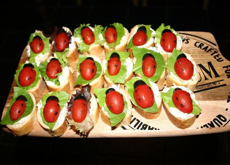 Lieveheersbeestjes gezonde hapjes. Stokbroodjes met tomaat, zwarte olijf, een blaadje sla en een ondergrondje van komkommer/kaas/kruidensalade.  Heerlijk en doet het goed op een feestje!