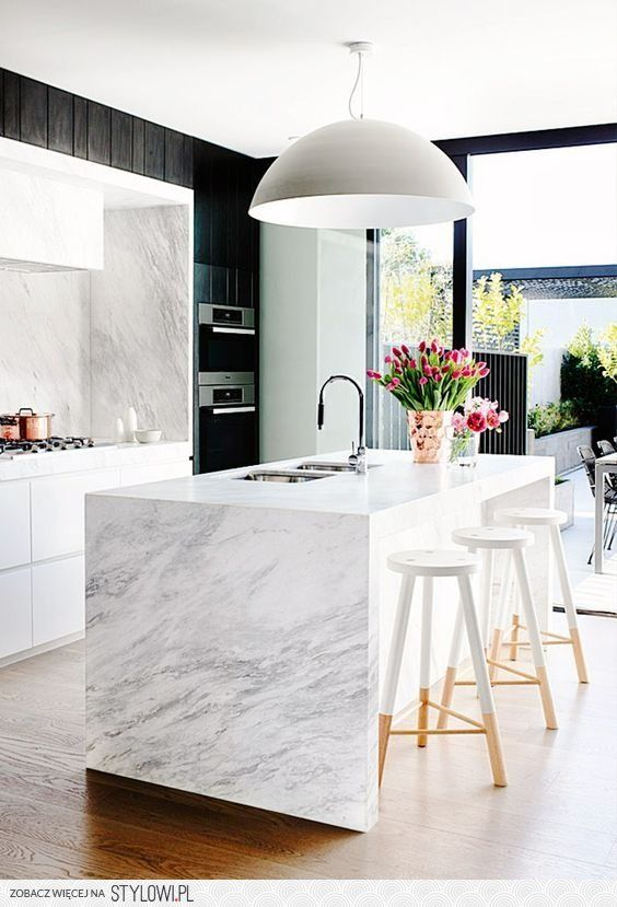 Natural materials in modern shapes marble and wood bring organic charm to this very modern kitchen
