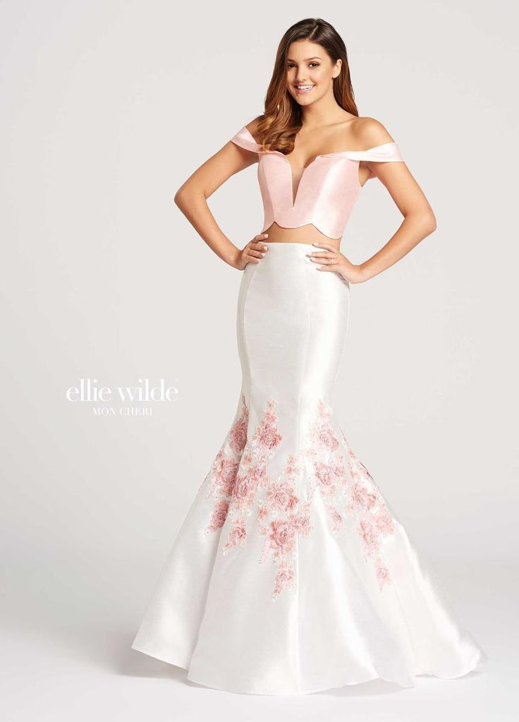 Style EW118041 from Ellie Wilde for Mon Cheri is a formal 2-Piece sheer plunging V-neck Shantung trumpet Prom gown with floral Embroidered Lace Appliques on the skirt.