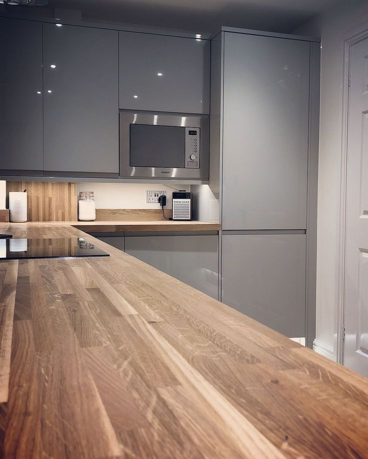 Eine moderne grifflose Küche mit Holzarbeitsplatte und Hochglanzküchenschränken …
