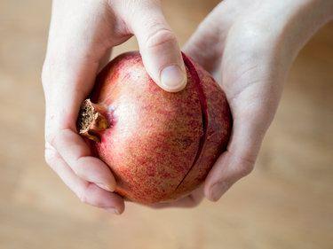 Obere und untere Hälfte gegeneinander drehen, um den Granatapfel zu öffnen.