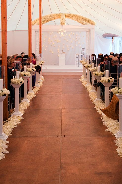 White rose petals and pillar candles in glass vases line a wooden aisle.