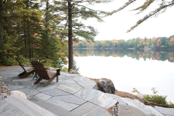 """This inland lake patio utilizes 3/4"""" thickness oversized Muskoka granite flagstone installed with a 1"""" sawn joint style that provides a random linear look. The calibrated oversized Muskoka Rock Company flagstone creates a crisp infinity patio edge and a smooth surface for patio chairs, tables and entertaining."""