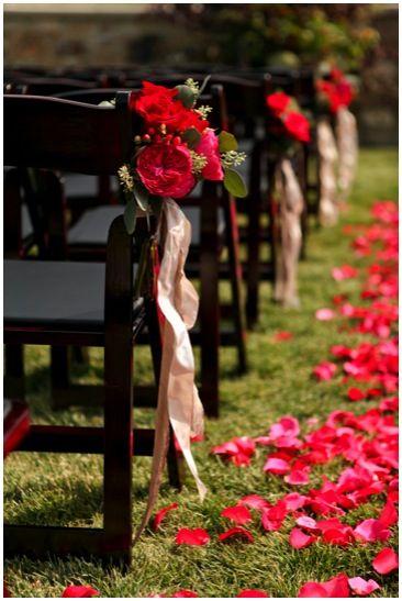 Nave com arranjos de flores vermelhas e fitas de cetim.  Casamentos únicos: inspiração rústica em vermelho | Paperland & Co.