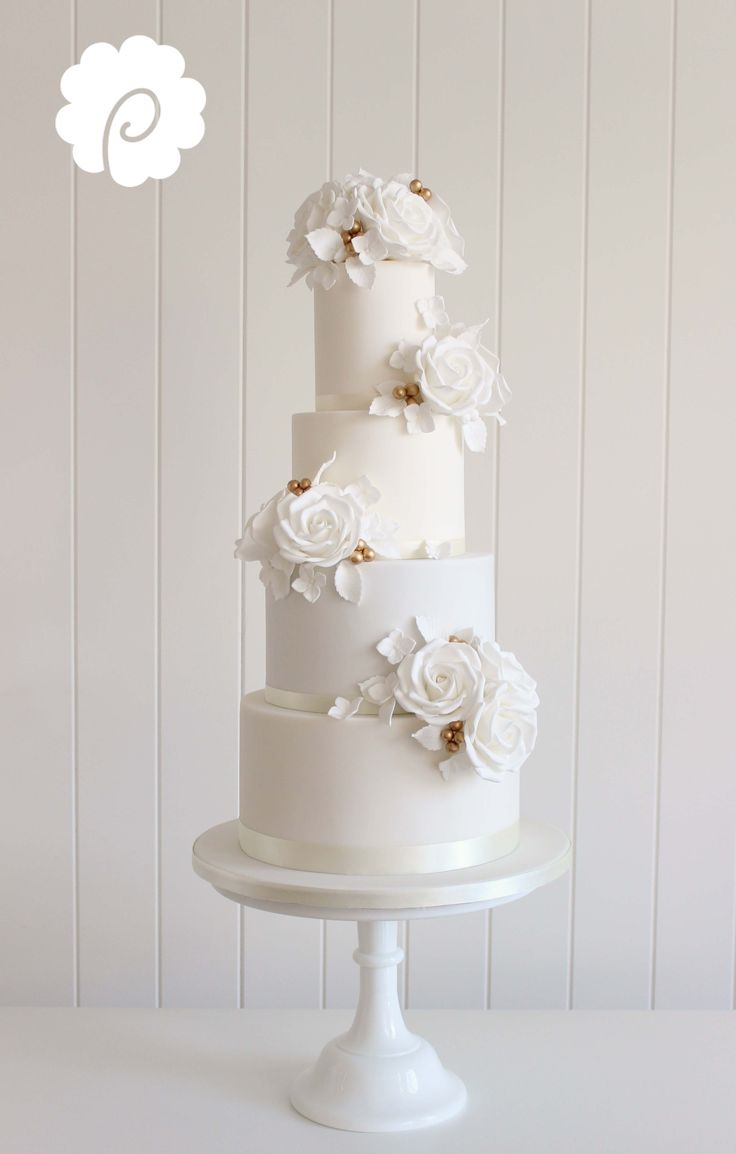 A clean white on white sugar rose wedding cake with gold detail