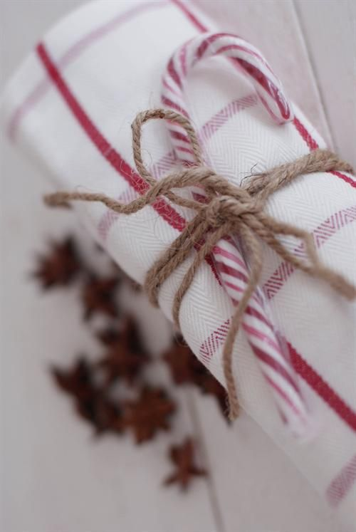 Red & white cloth napkin + twine + a candy cane | Holiday Party Planning