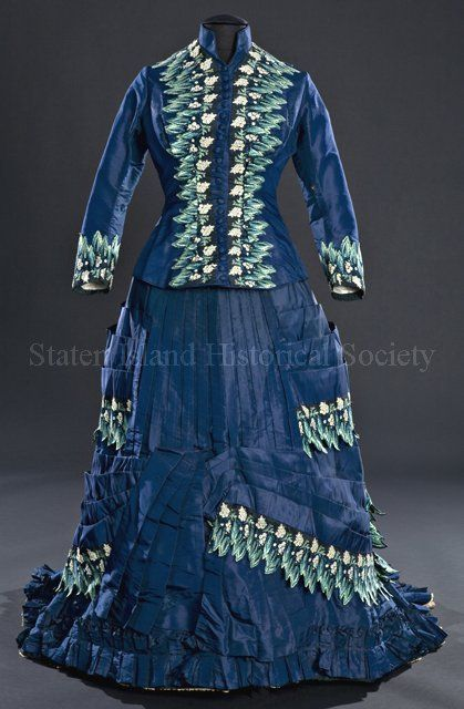 Woman's 2-piece day dress. Blue silk, trimmed with embroidery applique in shades of green, white, and yellow. Boned bodice has curved princess seams, front closure with covered buttons (one missing), standing collar, narrow coat sleeves, and weighted tail in back. Skirt is elaborately pleated, with asymmetrical detail in the front, asymmetrical skirt drapery in the back, and a box ruffle at the hem. Skirt is gathered in center back and has a long train. Floral and leaf machine embroidery