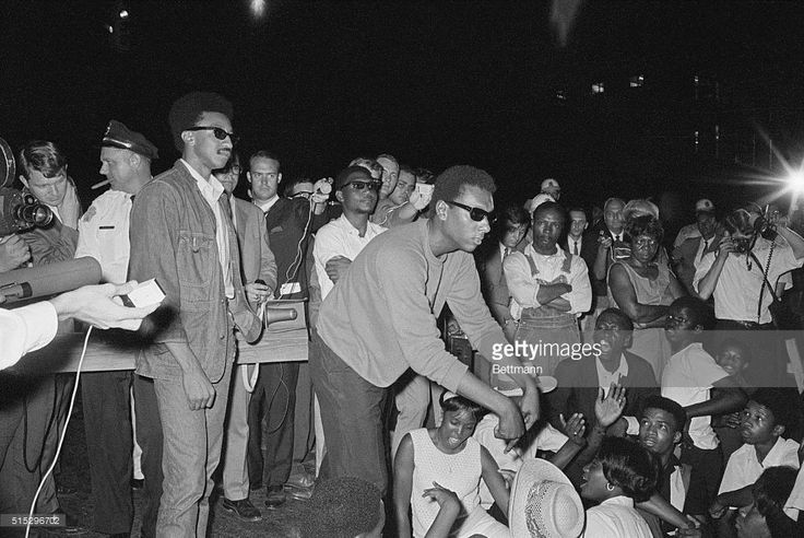 Student Nonviolent Coordinating Committee (SNCC) leader Stokely Carmichael points to the ground and tells African American student marchers to sit in the street after an attempted demonstration march on the Alabama Capitol was stopped by police a block away from their objective.