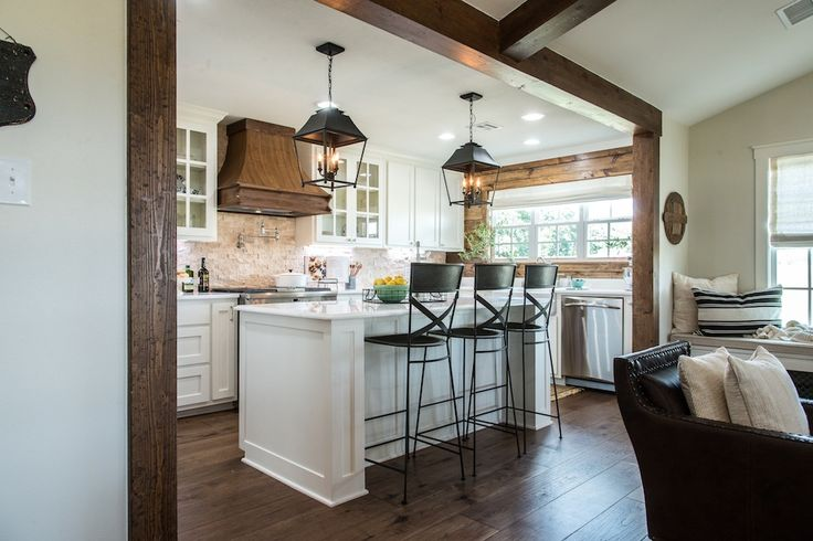 The kitchen was dark and the footprint was way too small for their needs as a family. We opened it up and did this wooden cased opening that matched the stain of the main living space's beams. We also tied in a shiplap wall and a wooden vent hood to warm up all of the white.