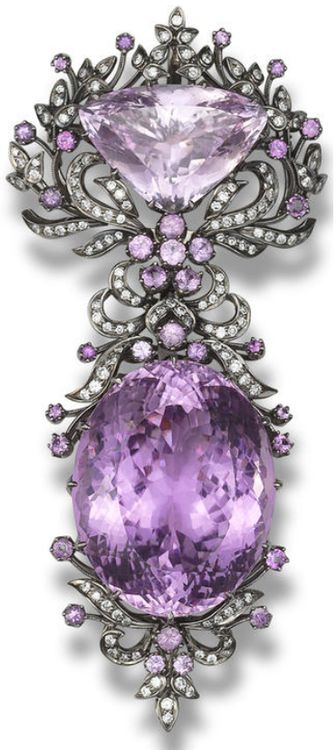 A kunzite and diamond brooch.  Designed as a detachable brooch, which can be worn as two separate pendants, set with an oval mixed-cut and a triangular mixed-cut kunzite, within a foliate surround set with circular-cut kunzites and brilliant-cut diamonds, mounted in 18k blackened gold, the oval kunzite estimated to weigh approximately 100.00 carats, the triangular kunzite estimated to weigh approximately 25.00 carats, the diamonds estimated to weigh approximately 1.36 carats in total…