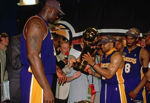 Derek Fisher #2 and Shaquille O'Neal #34 of Los Angeles Lakers present Lakers owner Jerry Buss with the Championship trophy after winning the NBA Title by defeating the Philadelphia 76ers in Game 5 of the 2001 NBA Finals played June 15, 2001 at the First Union Center in Philadelphia, Pennsylvania.