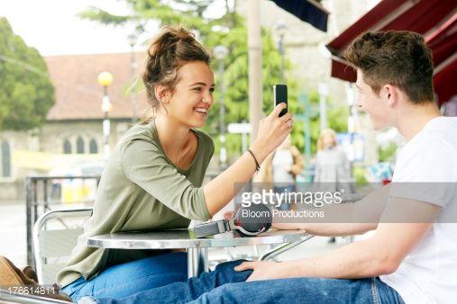 Foto de stock : Teenager taking a photo of friend on a smart phone