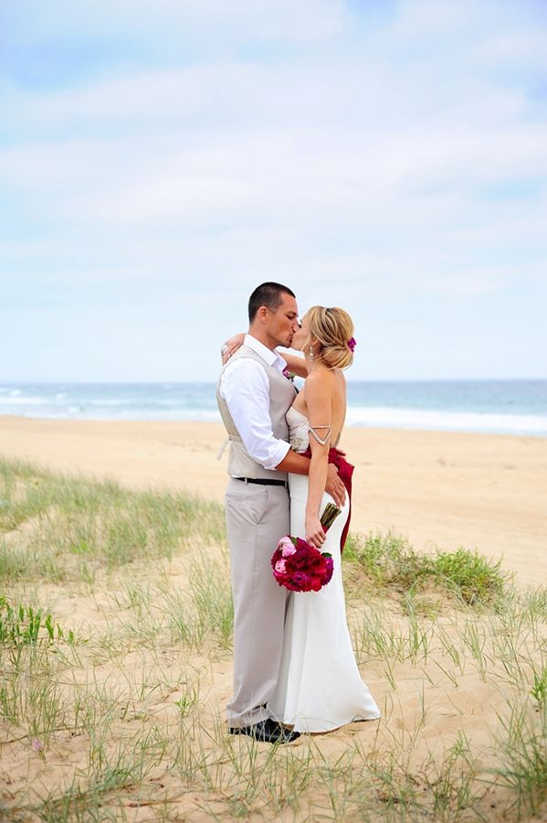 bride and groom kiss on a beach near wollongong with blue sky