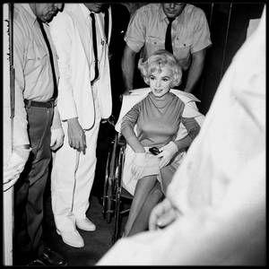 """11 Juillet 1961 / (PART III) Marilyn sortant du """"Manhattan Polyclinic Hospital"""", où elle vient d'y subir l'ablation de la vésicule biliaire. Elle porte une robe de couleur rose de chez PUCCI."""