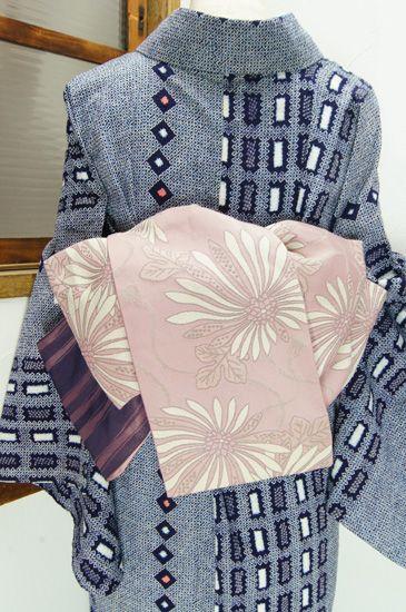 桜の花びらのようなごく淡いピンク色に、大輪の菊花と飾り紐の古典文様が優美な詩情をさそう化繊の半幅帯です。 #kimono