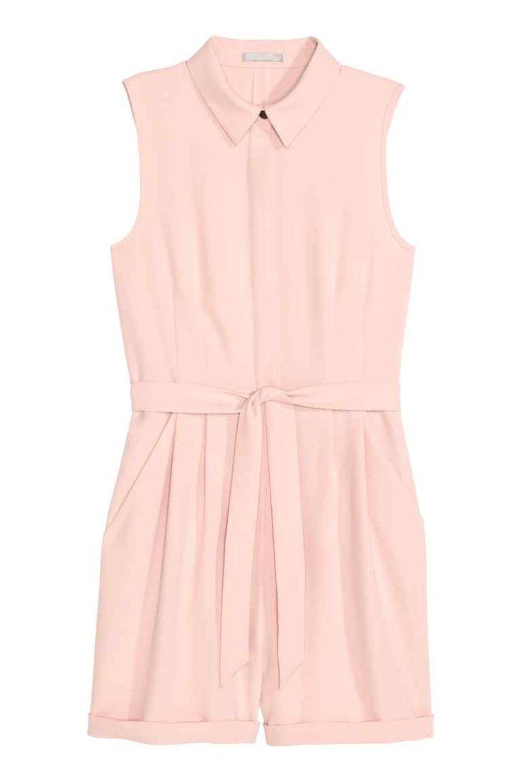 H&M : Combi-short habillé: Combi-short habillé en tissu crêpé. Modèle sans manches avec col et boutonnage dissimulé devant. Découpe à la taille et ceinture à nouer amovible. Fermeture à glissière dissimulée sur le côté. Plis plats devant et revers cousu en bas de jambe.