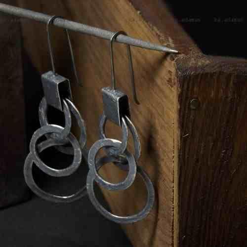 Długie, proste kolczyki wykonane z mocno oksydowanego (przyciemnionego), drapanego, przecieranego srebra próby 925. Ogniwa nieregularne, młotkowane. Długość całkowita kolczyków 7cm. w kuferart.pl